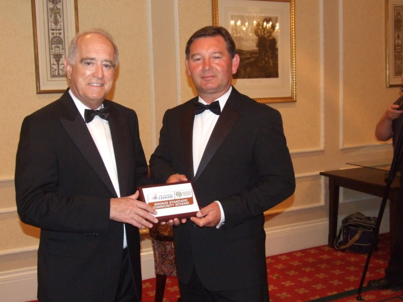 Community Manager Peter Aitken receives his department's Bronze Award from Lord Mawhinney