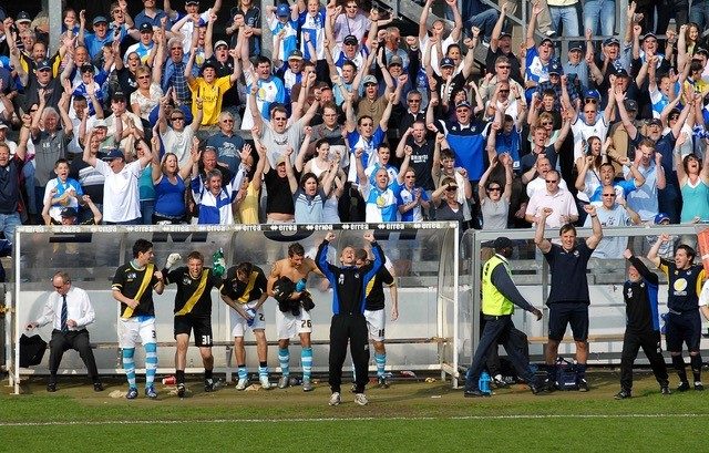 Celebrations on the bench at the end of the Swindon game. Photo Credit Neil Brookman